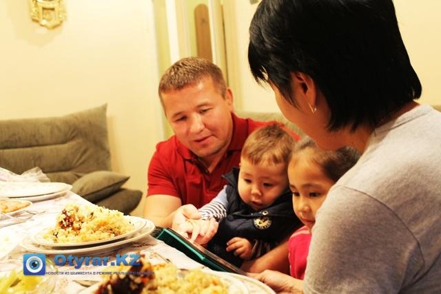 Аскар Клушев, бронзовый призер чемпионата мира 2012 года и чемпион мира 2010 года по вольной борьбе среди ветеранов. На фото вместе со своей семьей смотрят альбом.