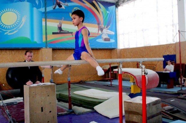 Юный гимнаст выполняет упражнение на параллельных брусьях