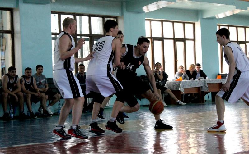 Игрок шымкентской команды пытается прорваться через заслон соперника к кольцу.