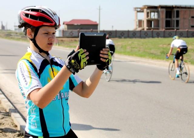 Юный спортсмен решил запечетлить выступление  велогонщика из своей команды.