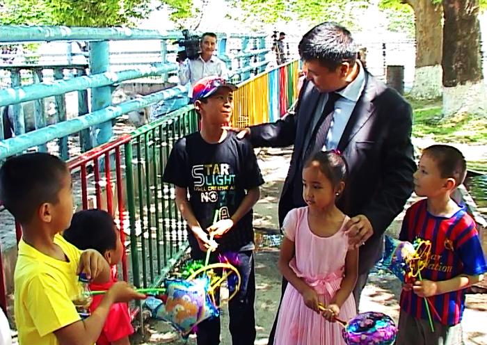 Дети с удовольствием ели подаренные лакомства и на перебой задавали вопросы акиму