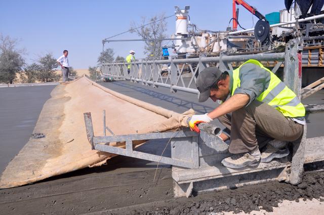 Рабочие укладывают бетон на последнем участке дороги