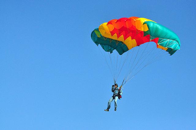 Парящий в небе парашютист