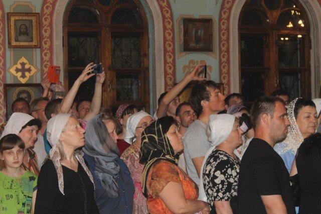 Стоя в очереди, люди снимают действо на мобильные телефоны
