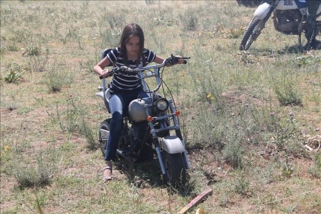 Девочка совсем недавно села на мотоцикл, но у же с легкостью управляет железным конем