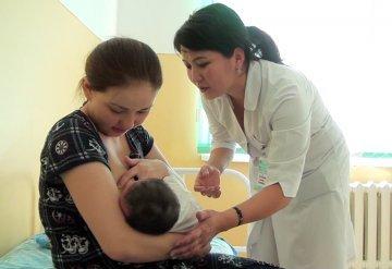 Молодая мама учится правильно кормить ребенка грудью