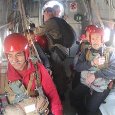 Савченко прикрепляет страховочные карабины всем парашютистом