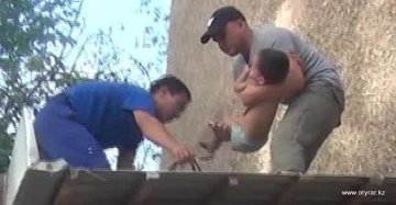 Спасательная бригада спускает малыша с крыши магазина