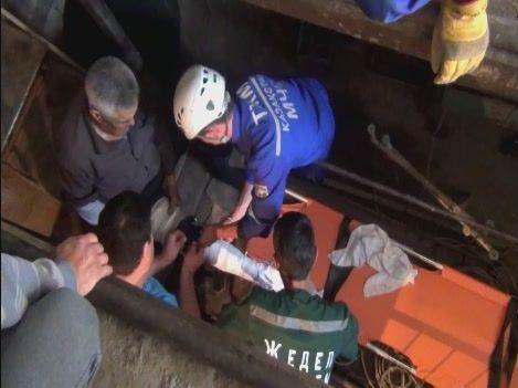 Спасатели достают женщину из септика