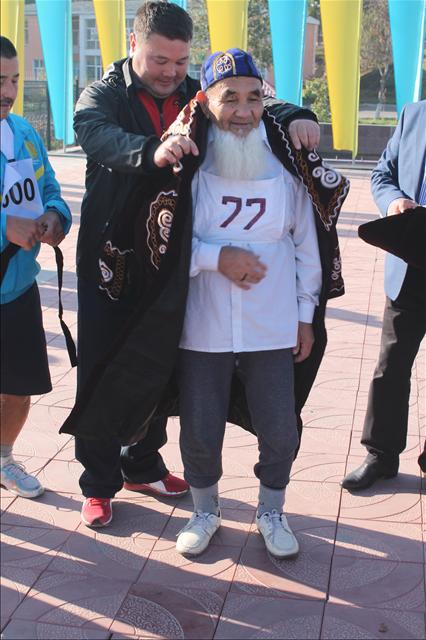 От имени акима города Дархана Сатыбалды самому пожилому участнику марафона одели чапан, вручили диплом участника и ценный приз