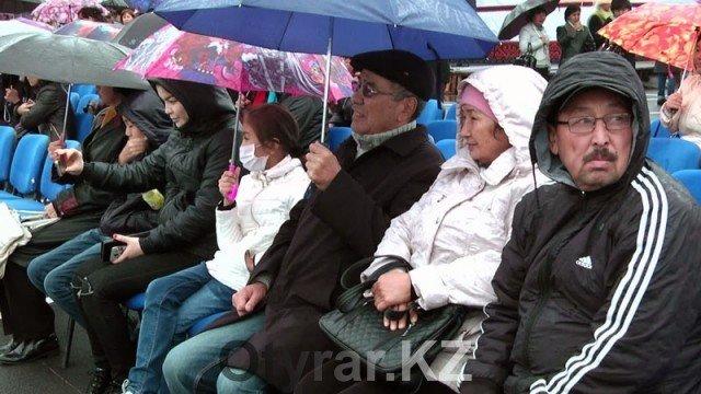 В Шымкенте отпраздновали День города. Дождь. Люди под зонтами