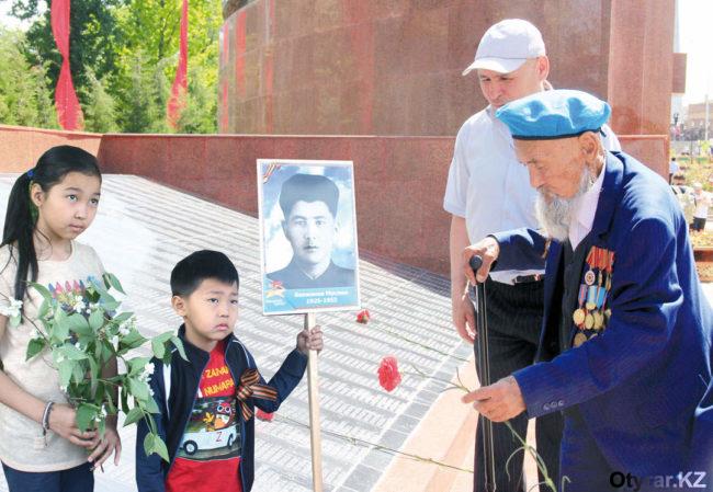 Это фото украсило первую страницу праздничного номера газеты «РАБАТ». На нём изображена группа людей на мемориале Славы...