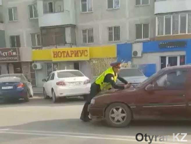 Полицейский задерживает автомобиль